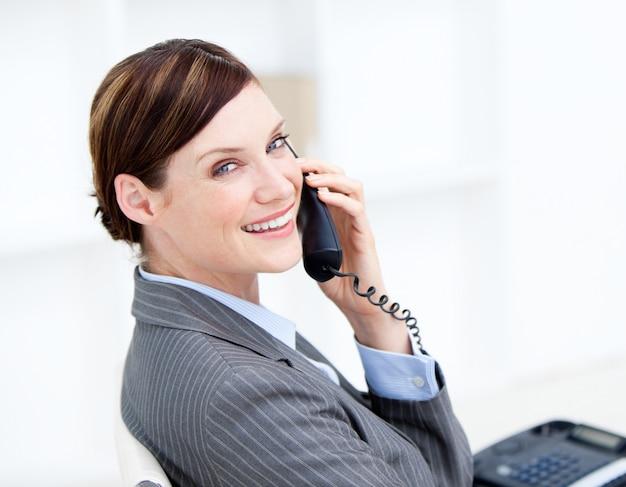 Überzeugte geschäftsfrau am telefon, das an ihrem schreibtisch sitzt
