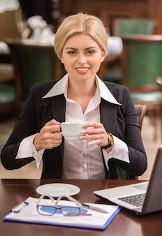 Überzeugte geschäftsfrau, die am tisch im café sitzt.