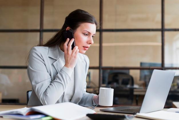 Überzeugte geschäftsfrau, die auf mobiltelefon spricht und arbeitsplatz betrachtet und kamera