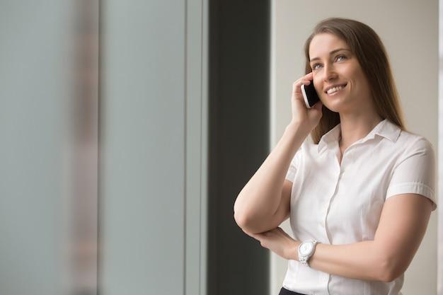 Überzeugte geschäftsfrau, die auf mobiltelefon spricht