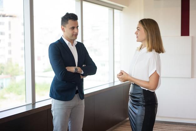 Überzeugte geschäftsfrau, die mit männlichem kunden im modernen büro spricht.