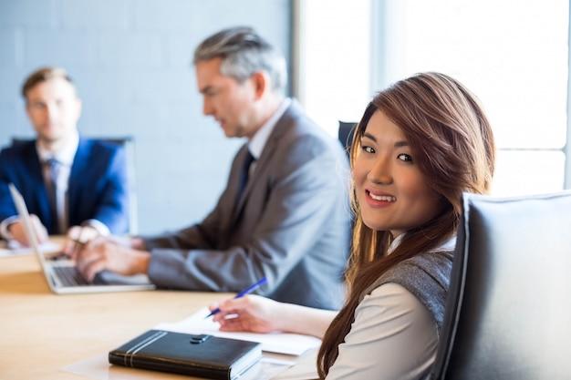 Überzeugte geschäftsfrau in einem konferenzsaal während der sitzung im büro