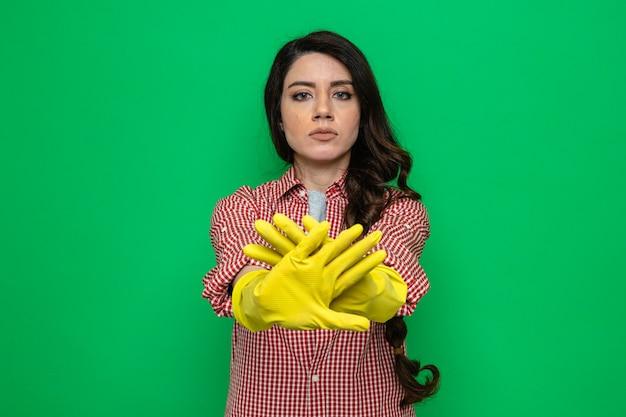 Überzeugte hübsche kaukasische putzfrau mit gummihandschuhen, die ihre hände kreuzen und stoppschild gestikulieren