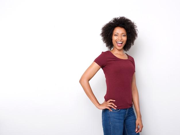 Überzeugte junge frau, die gegen weißen hintergrund und das lachen aufwirft