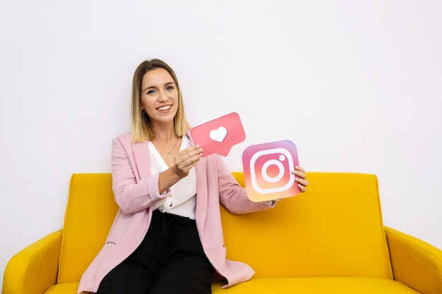 Überzeugte junge frau, die instagram hält und ikone mag