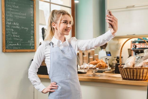 Überzeugte junge frau, die selfie vom handy in ihrer kaffeestube nimmt