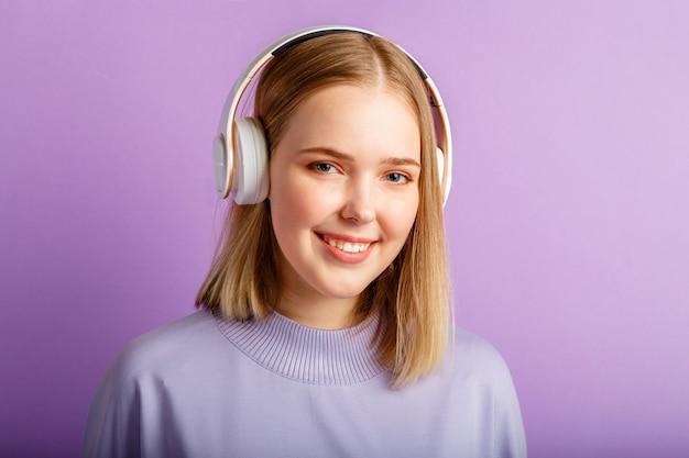 Überzeugte junge frau im kopfhörerporträt. schöne ernste frau mit blonder frisur genießen sie liedmusik im kopfhörer einzeln auf violettem farbhintergrund. platz kopieren.