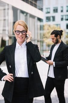 Überzeugte junge geschäftsfrau, die am handy mit ihrem kollegen arbeitet am hintergrund spricht