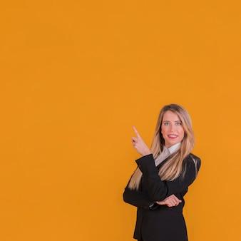 Überzeugte junge geschäftsfrau, die aufwärts ihren finger gegen einen orange hintergrund zeigt
