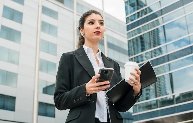 Überzeugte junge geschäftsfrau, die außerhalb des unternehmensgebäudeholdingmobile steht; einwegkaffeetasse und -mappe in der hand