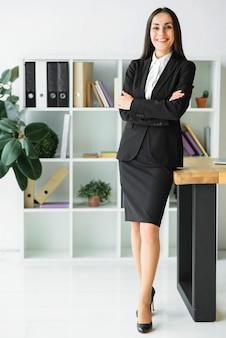 Überzeugte junge geschäftsfrau, die im büro mit ihren armen gekreuzt steht