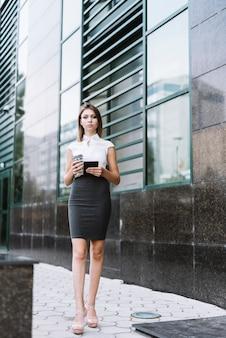 Überzeugte junge geschäftsfrau, die vor dem bürogebäude hält wegwerfkaffeetasse und smartphone hält