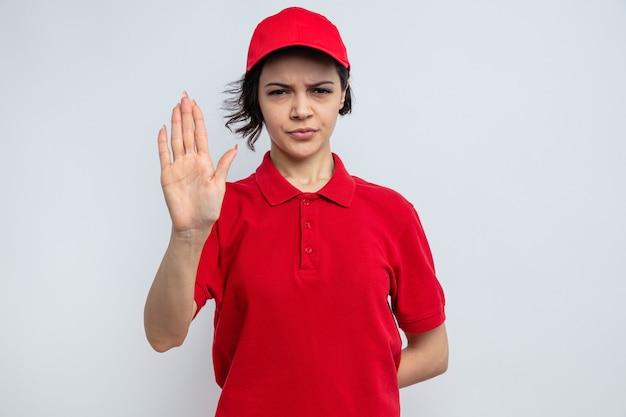 Überzeugte junge hübsche lieferfrau, die stoppschild gestikuliert