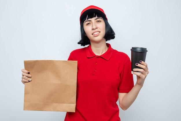 Überzeugte junge kaukasische lieferfrau, die lebensmitteltüte und pappbecher hält