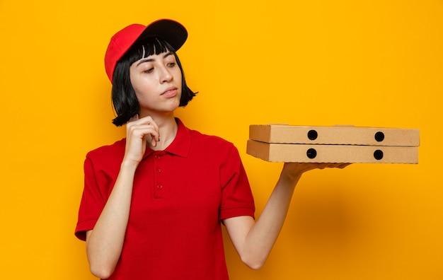 Überzeugte junge kaukasische lieferfrau, die pizzakartons hält und betrachtet