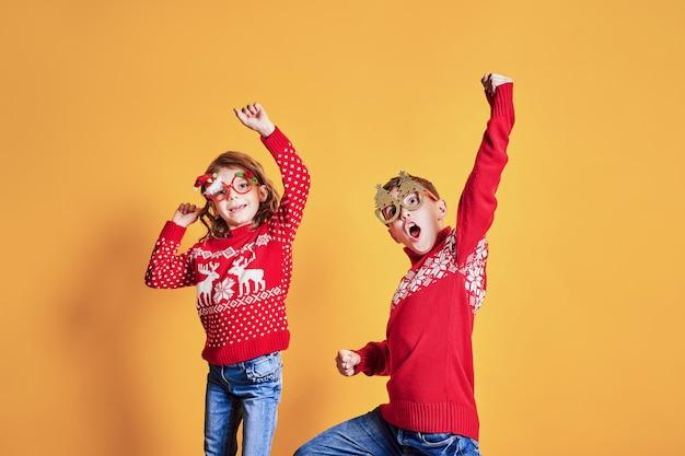 Überzeugte kinder in den warmen roten weihnachtsstrickjacken und in verzierten gläsern, die kamera auf gelbem hintergrund betrachten
