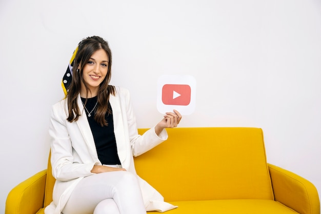 Überzeugte lächelnde junge frau, die youtube ikone zeigt