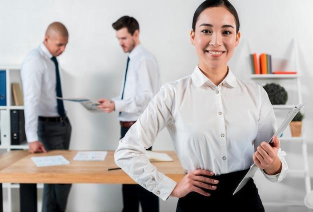 Überzeugte lächelnde junge geschäftsfrau, die in der hand klemmbrett mit dem geschäftsmann zwei steht am hintergrund hält