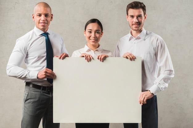 Überzeugte lächelnde junge geschäftsfrau mit seinen zwei kollegen, die leeres plakat halten