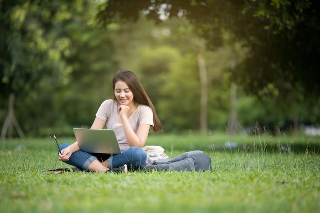 Überzeugte lächelnde recht junge frau, die auf arbeitsplatz in im freien mit laptop sitzt. arbeitskonzept