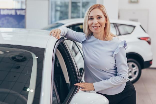 Überzeugte reife geschäftsfrau, die neues automobil an der verkaufsstelle kauft