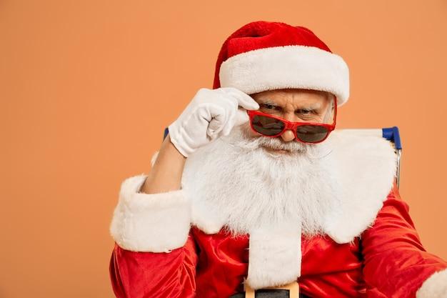 Überzeugte santa claus, die kamera durch sonnenbrille betrachtet