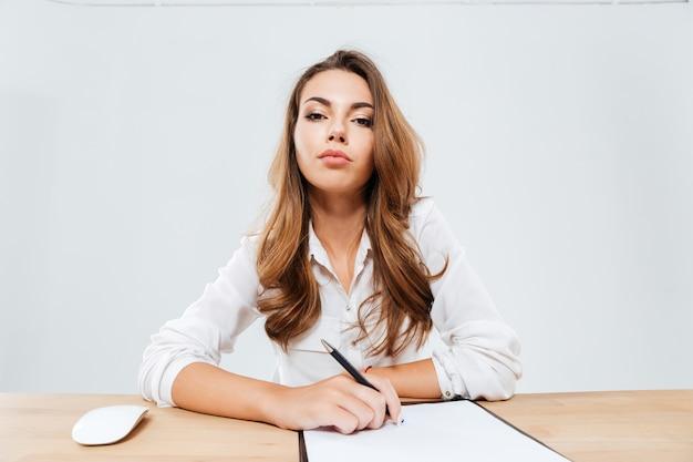 Überzeugte schöne geschäftsfrau, die am tisch über weißem hintergrund sitzt
