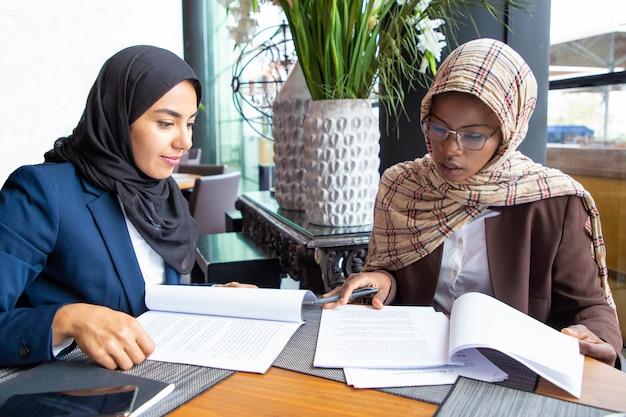 Überzeugte weibliche fachleute, die dokumente überprüfen
