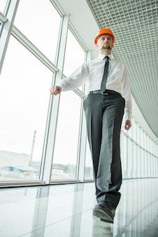 Überzeugter architekt mit sturzhelm geht in büro.