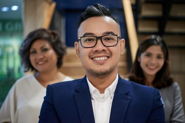 Überzeugter asiatischer geschäftsmann, der für kamera und weibliche kollegen hinten stehen lächelt