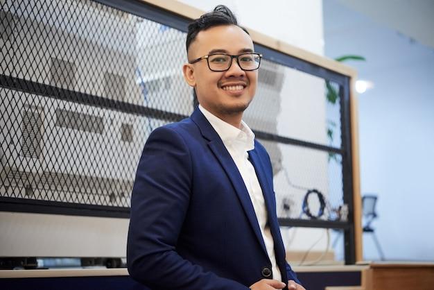 Überzeugter asiatischer geschäftsmann in der klage, die im büro aufwirft