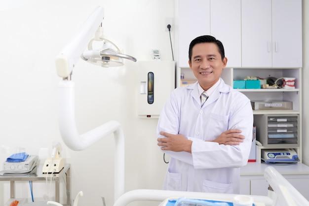 Überzeugter asiatischer männlicher zahnarzt von mittlerem alter, der in der klinik aufwirft