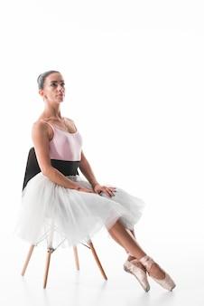 Überzeugter balletttänzer, der auf stuhl mit dem gekreuzten bein gegen weißen hintergrund sitzt
