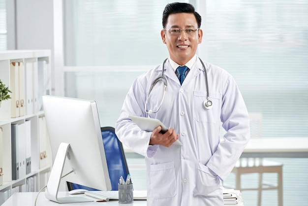 Überzeugter doktor, der die kamera hält den tablet-pc betrachtet
