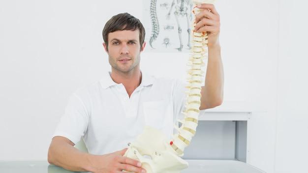 Überzeugter doktor, der skeleton modell in seinem büro hält