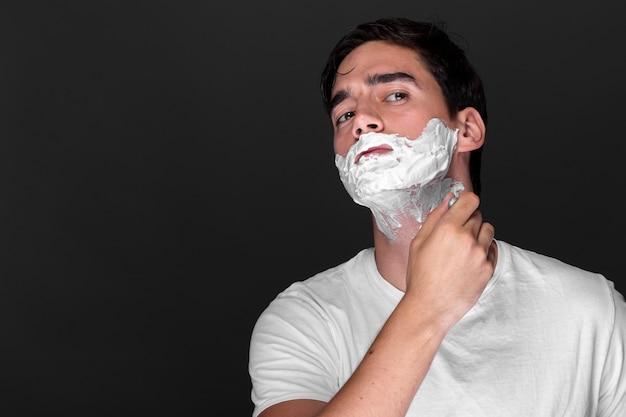 Überzeugter erwachsener mann, der seinen bart rasiert