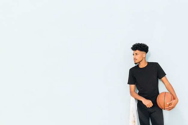 Überzeugter ethnischer mann, der basketball halten lehnend steht