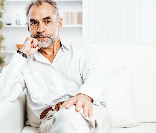 Überzeugter geschäftsmann, der auf couch im hellen büro sitzt. das foto hat einen leeren platz für ihren text