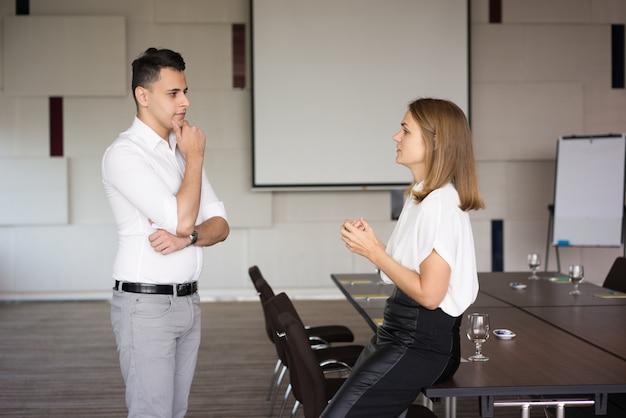 Überzeugter geschäftsmann, der auf seinen weiblichen kollegen im konferenzsaal hört.