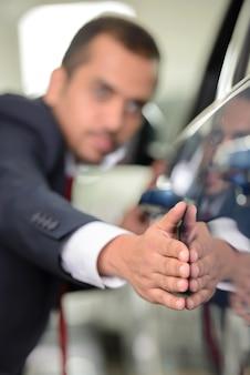 Überzeugter geschäftsmann, der ein auto an der verkaufsstelle überprüft