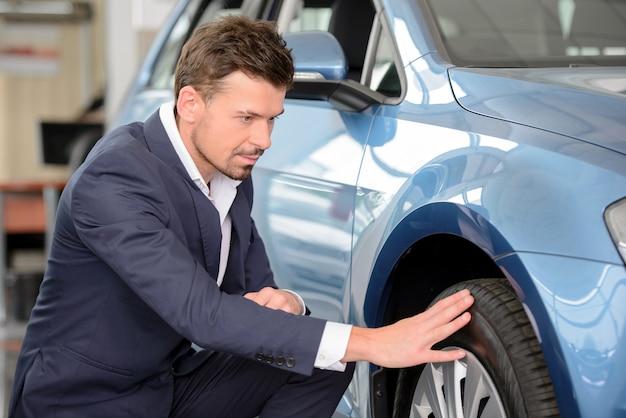 Überzeugter geschäftsmann, der ein auto an der verkaufsstelle überprüft.