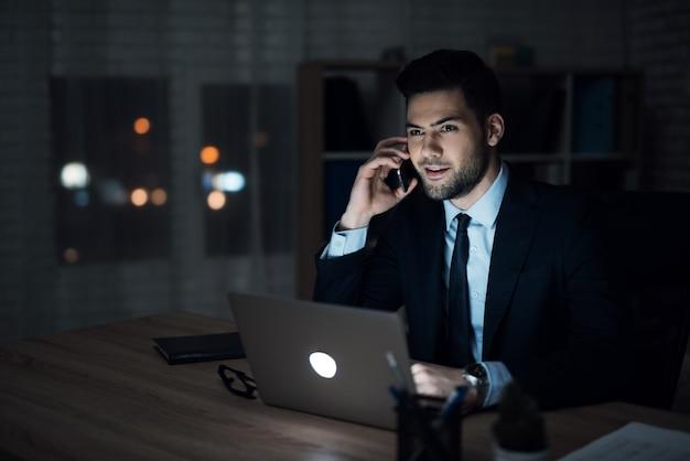 Überzeugter geschäftsmann working im büro nachts