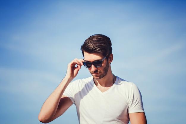 Überzeugter gutaussehender mann in der sonnenbrille