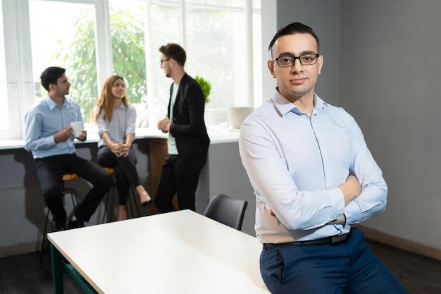 Überzeugter hübscher geschäftsführer, der im konferenzzimmer aufwirft