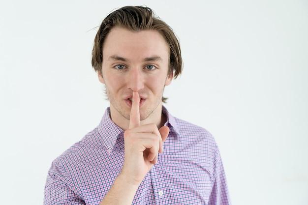 Überzeugter hübscher junger mann im zufälligen hemd, das ruhezeichen macht