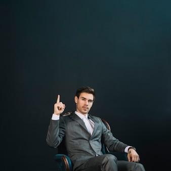 Überzeugter intelligenter junger geschäftsmann, der auf dem lehnsessel zeigt finger aufwärts gegen schwarzen hintergrund sitzt