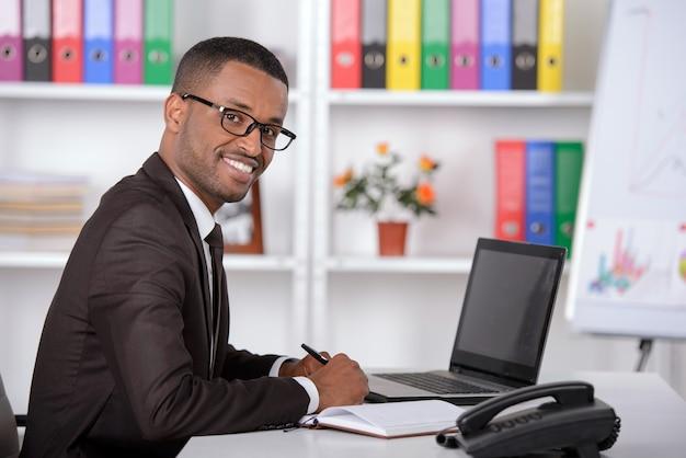 Überzeugter junger afrikanischer geschäftsmann, der in seinem büro arbeitet.