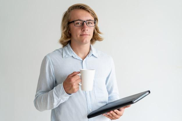 Überzeugter junger geschäftsanalytiker, der kaffeepause genießt