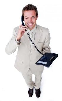 Überzeugter junger geschäftsmann, der am telefon spricht