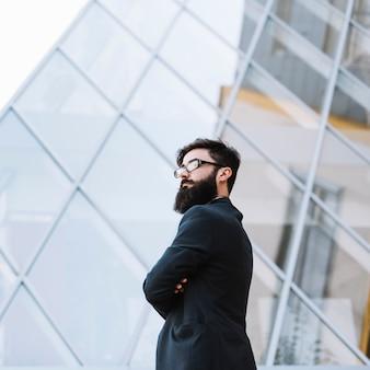 Überzeugter junger geschäftsmann, der vor glasgebäude steht